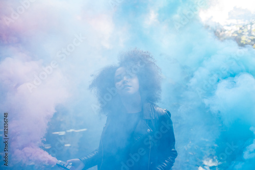 Young woman with colored smoke bombs - Buy this stock photo