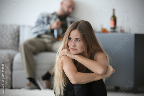 Poster de jardin Bar Young woman and blurred man with bottle of alcohol at home