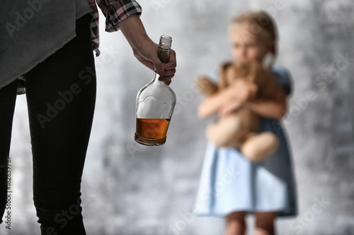 Fotografia  Woman with bottle of alcohol and blurred girl on grey background