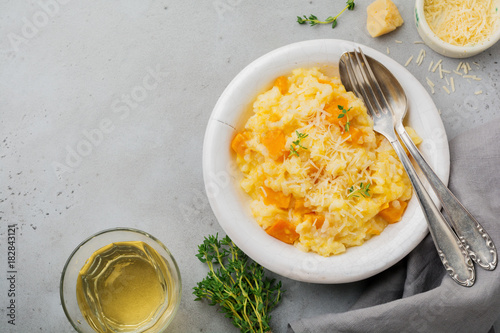 Pumpkin risotto with thyme, garlic, parmesan cheese and white wine on gray concrete or stone  background. Selective focus. Rustic style. Top view.