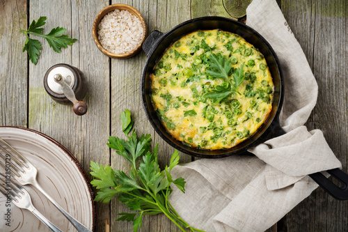 Fritatta with potatoes, green peas and herbs in an iron frying pan on an old wooden background. Selective focus. Rustic style.Top view.