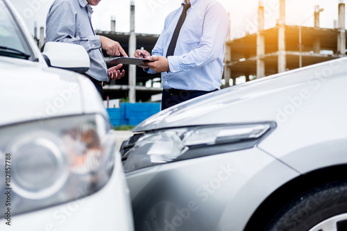Insurance agent writing on clipboard while examining car after accident claim being assessed and processed Canvas Print