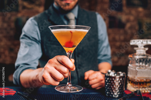 Fotografía  Bartender serving manhattan cocktail in martini glass