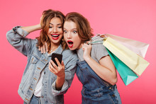 Shocked Two Women Friends Holding Shopping Bags Using Mobile Phone.