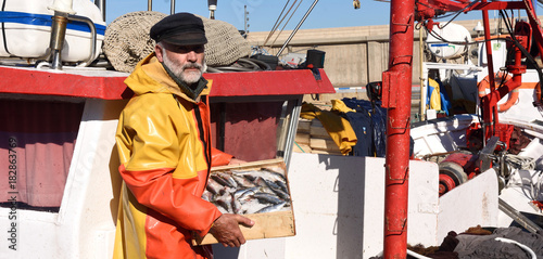 Canvas Print fisherman with a fish box inside a fishing boat