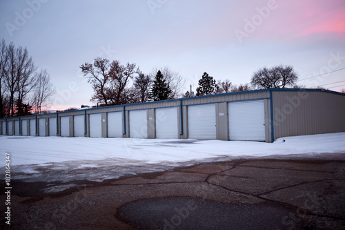 Fotografia Row of garages in winter snow at sunset