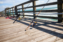 Fishing Rods On A Wooden Marine Jetty Or Pier