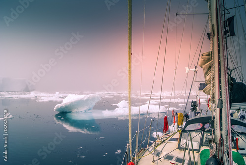 Fotobehang Poolcirkel Greenland, arctic: sailing boat trough the iceberg, risk, danger