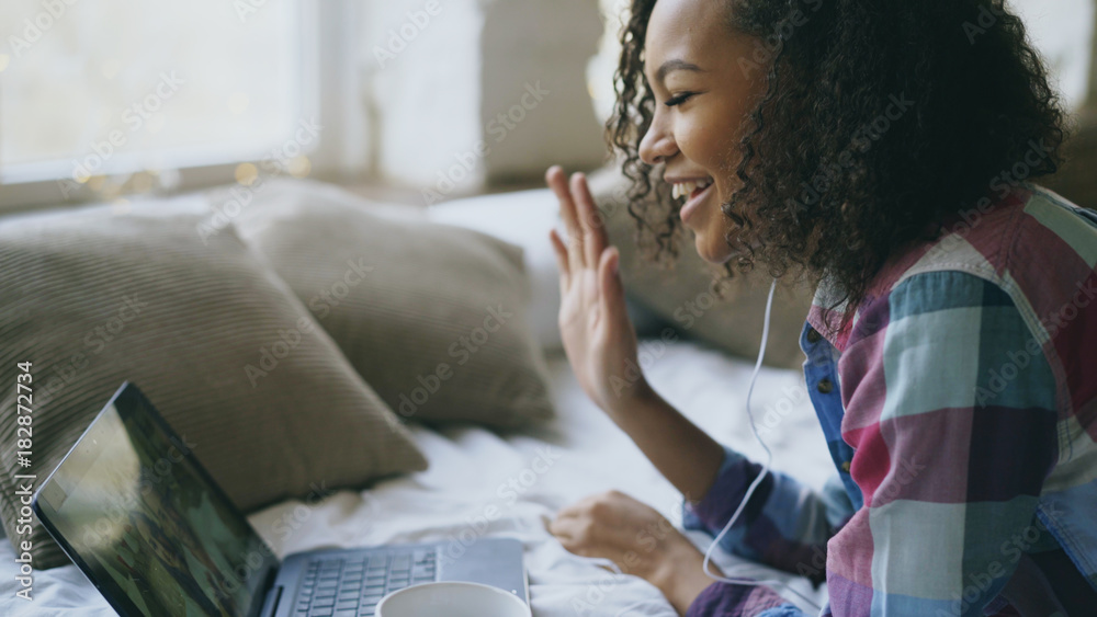 Fototapeta Curly african american young woman having video chat with friends using laptop camera while lying on bed
