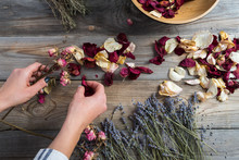 Hands Of A Florist Spreading Dry Herbs On A Work Surface