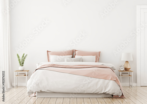 Fotografia  Light, cute and cozy home bedroom interior with unmade bed, pink plaid and cushions on empty white wall background