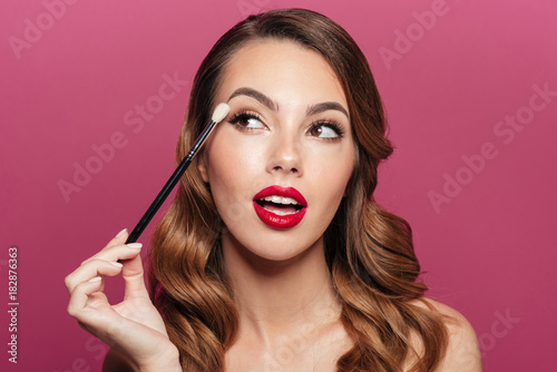 Fotografía  Young pretty lady making make up with brush for eyes isolated