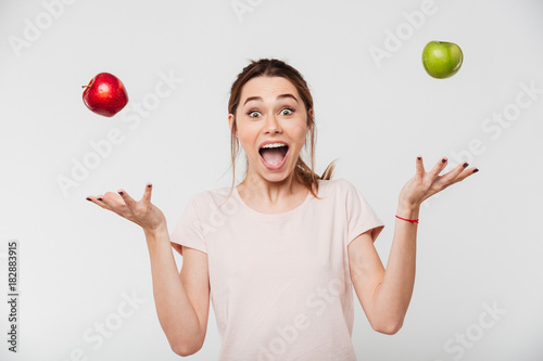 Cuadros en Lienzo Portrait of a happy girl throwing apples in the air