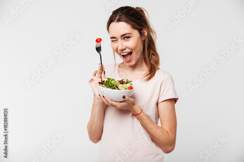 Fotografía Portrait of a happy playful girl eating fresh salad