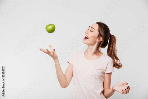 Portrait of a smiling girl throwing apple in the air Canvas