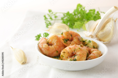 shrimps with garlic, olive oil and parsley in sherry sauce in a white bowl, spanish tapas appetizer gambas al ajillo, white napkin and herb garnish in the background, copy space