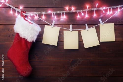 Obraz na plátně  Four blank paper labels and Santa sock on wooden background