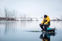 Man Ice Fishing On A Frozen Lake.