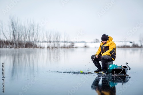 Man ice fishing on a frozen lake.