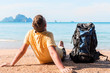 tourist with a large backpack relaxes on the beach near the sea with a beautiful view of the mountains