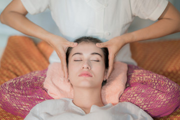 Fototapeta na wymiar Portrait of fresh and beautiful young Asian woman taking Thai head massage spa in spa salon.