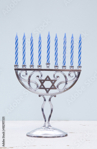 Hanukkah Menorah with a Simple Blue Background on a Distressed Wooden Table Wallpaper Mural