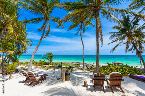Chairs under the palm trees on paradise beach at tropical Resort. Riviera Maya - Caribbean coast at Tulum in Quintana Roo, Mexico