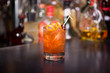 Gourmet old fashion cocktail with spiral garnish and blurry bottle background