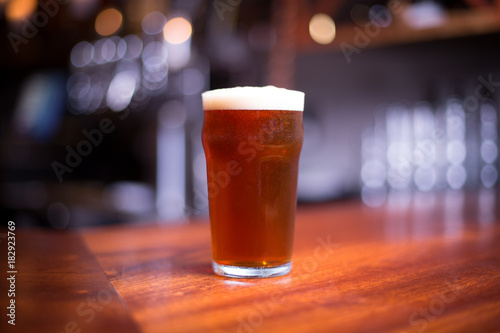 Photo Pint of India pale ale on a wood counter at a bar