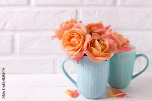 Zdjęcie XXL Świeże pomarańczowe róże w błękitnych filiżankach