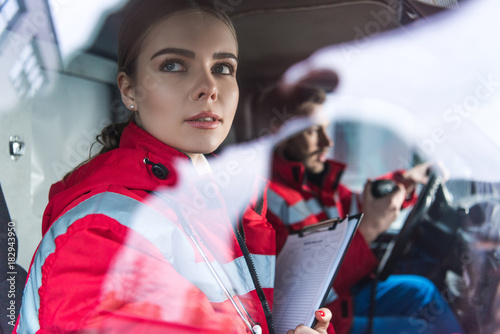 Photo attractive young paramedic sitting in ambulance and looking away