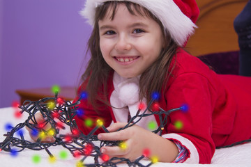 little girl with santa hat and christmas lights