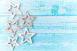 Gingerbread cookies, snowflakes hanging with ribbon over a blue wood background. Free space copyspace for your text.