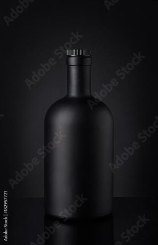 Leinwand Poster Black whiskey bottle on dark background