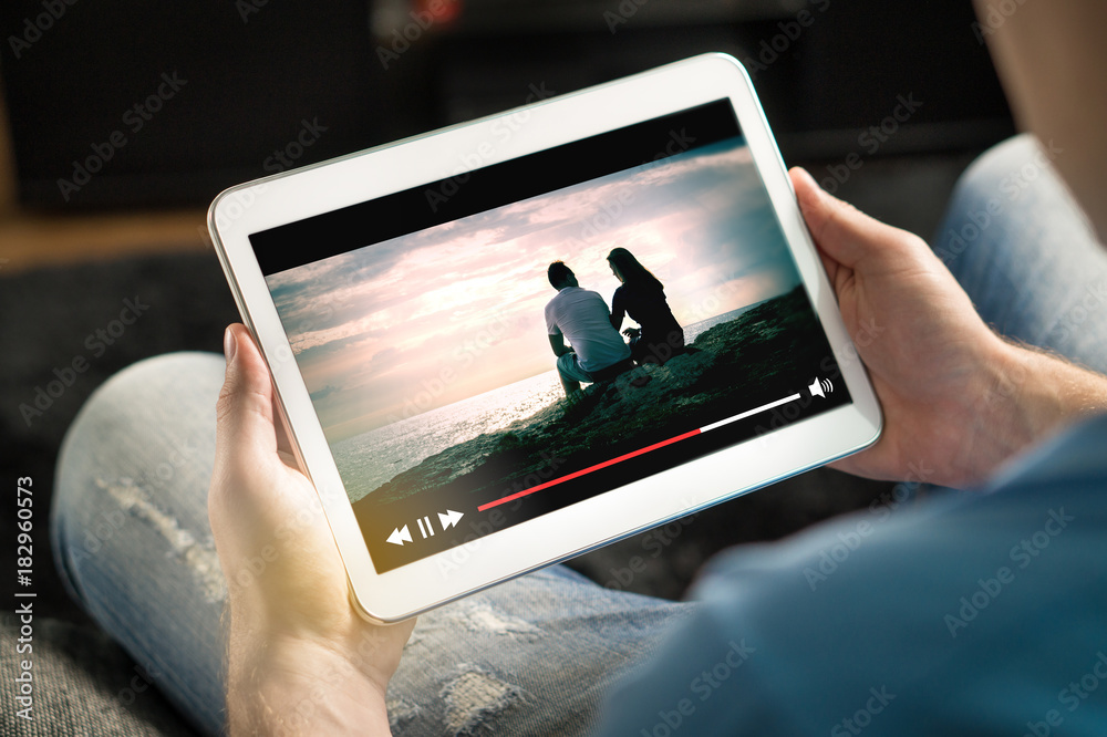 Fototapeta Online movie stream with mobile device. Man watching film on tablet with imaginary video player service.