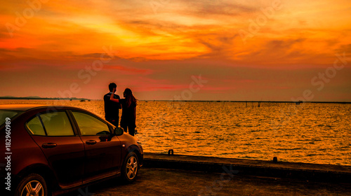 Stickers pour porte Orange eclat Silhouette of happiness couple standing by the car at the seaside at sunset. Beautiful orange sky and clouds