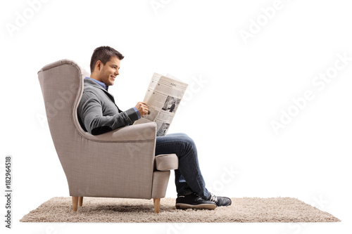 Fotografie, Obraz  Young guy seated in an armchair reading a newspaper