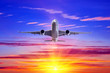 canvas print picture - Airplane take off against the background of evening sunset rays.