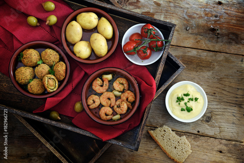 spanish tapas as party appetizers, baked olives, prawn shrimps, potatoes, tomato and garlic dip on a wooden tray with a red napkin on rustic wood, warm dark country style, flat top view from above