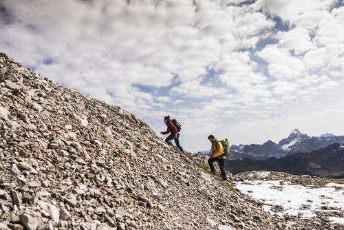 Germany, Bavaria, Oberstdorf, two hikers walking up stony mountain