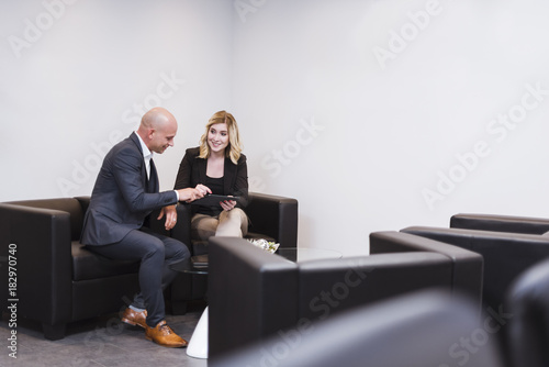 Businessman and businesswoman sitting on couch sharing tablet