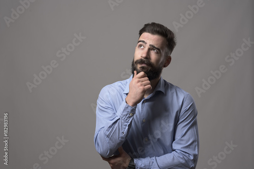 Cuadros en Lienzo Young adult hipster business man thinking and looking up at copyspace while touching beard against gray studio background