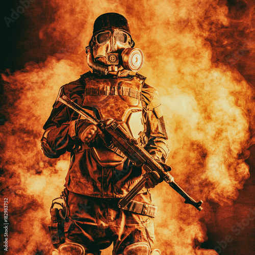 Cuadros en Lienzo  Futuristic nazi soldier in fire and smoke gas mask and steel helmet with schmeis