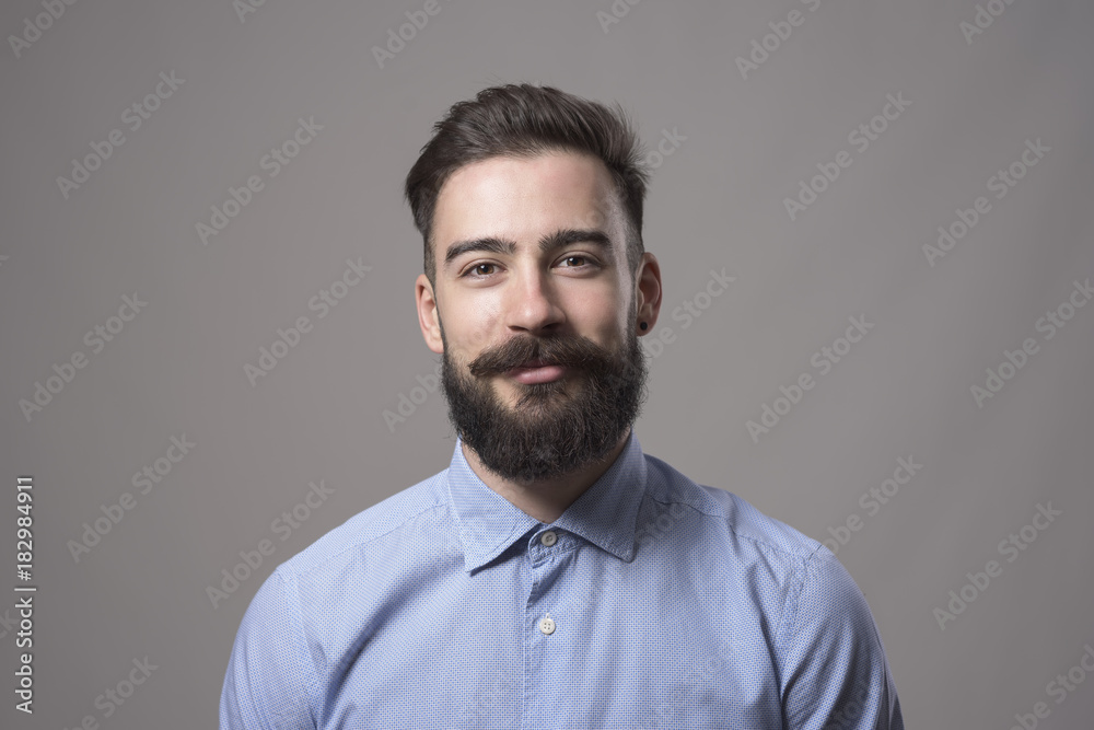 Fototapeta Horizontal  head and shoulder portrait of young bearded business man smiling at camera against gray studio background.