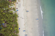 Aerial view of beautiful coastline of Indian ocean with tropical forest, sandy beach, calm blue water and fishing boats in Goa, Palolem beach