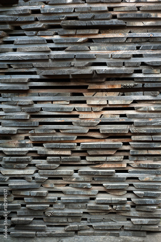 Láminas  Folded wooden brown and gray planks in a sawmill