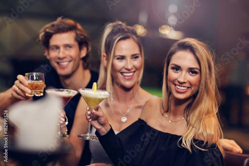 Obraz na plátne Group Of Friends Enjoying Drink in Bar