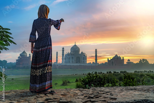 Beautiful girl points to Taj Mahal. Travel concept Canvas Print