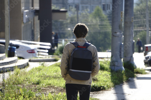 A young boy wearing a cap with a backpack walking through the city фототапет