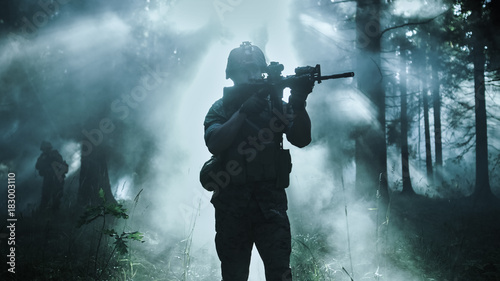 Fotografía  Silhouette of the Fully Equipped Soldier Moving Through Smokey Forest with Rifle Ready To Shoot